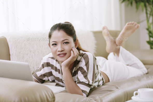 Girl with laptop resting on sofa - Stock Photo - Images