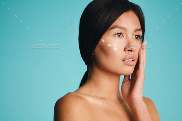 Portrait of beautiful Asian brunette girl with points of cream on cheek dreamily looking away - Stock Photo - Images
