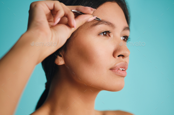 Side view of beautiful Asian brunette woman dreamily plucking eyebrows over colorful background - Stock Photo - Images