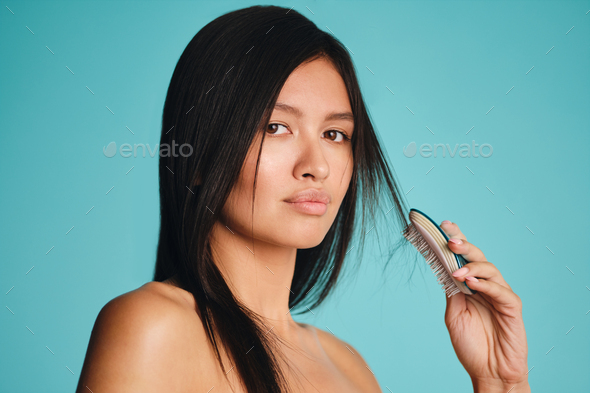 Beautiful Asian brunette girl confidently looking in camera combing hair over colorful background - Stock Photo - Images