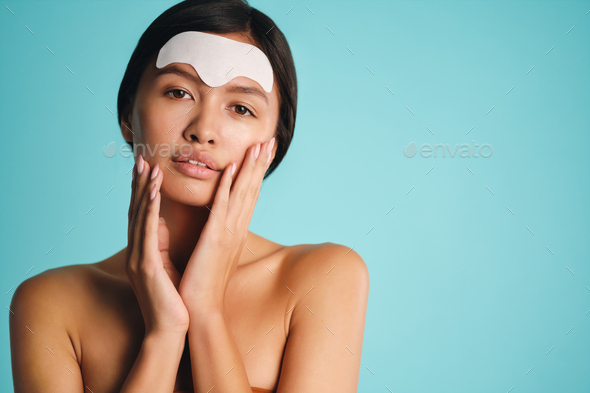 Beautiful Asian brunette girl applying facial mask sensually posing over colorful background - Stock Photo - Images