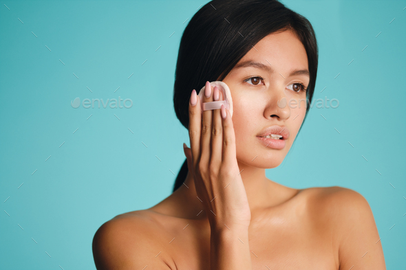 Beautiful Asian brunette girl dreamily looking away applying blusher on face with powder puff - Stock Photo - Images