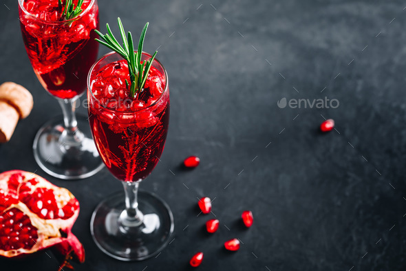 Pomegranate Champagne Cocktail with rosemary on gray concrete stone background - Stock Photo - Images