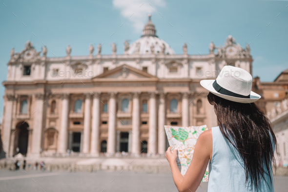 Happy young woman with city map in Vatican city and St. Peter's Basilica church - Stock Photo - Images