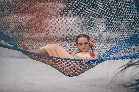 Adorable little girl swinging in hammock at beach - Stock Photo - Images