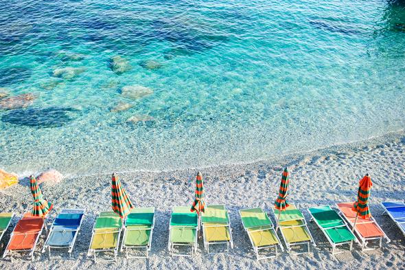 Empty beach with closed umbrellas on italian coast - Stock Photo - Images