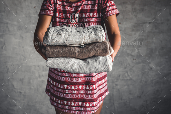 A girl in a Christmas dress holds a stack of sweaters. Warmth, comfort - Stock Photo - Images