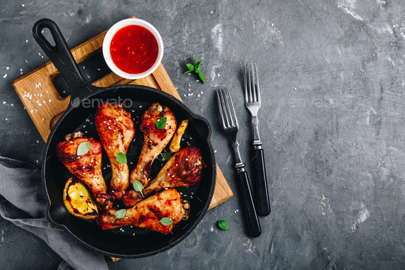 Roasted Lemon Chicken Legs with chili sauce and sesame in cast iron pan on dark stone background - Stock Photo - Images