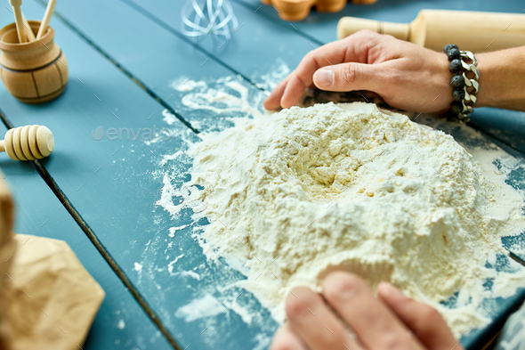 Man forming the dough on a floured surface and kneading it with his hands. - Stock Photo - Images