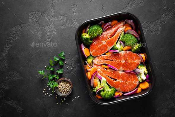 Salmon. Cooking fresh raw salmon fish steaks with vegetables, broccoli, carrot and onion - Stock Photo - Images