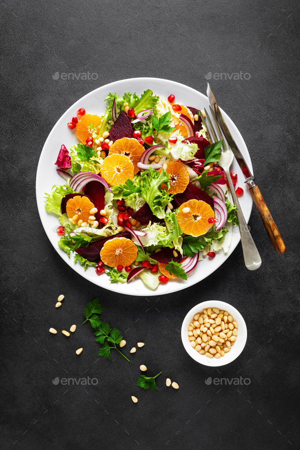 Christmas salad with boiled beet, red onion, tangerines, pomegranate, parsley, pine nuts and lettuce - Stock Photo - Images