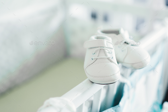 Baby shoes on baby bed - Stock Photo - Images