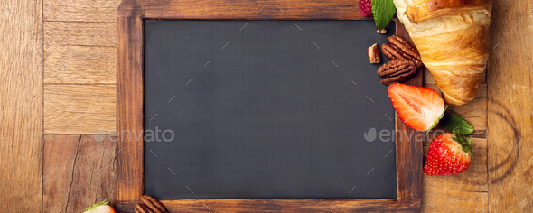 Black chalkboard with croissant and berries - Stock Photo - Images