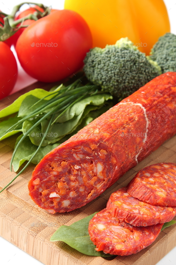 Spanish chorizo sausage with vegetables on a wooden board - Stock Photo - Images
