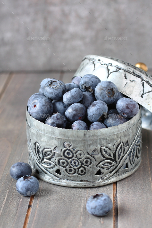 Fresh blueberries in small delicate metal casket on wooden background - Stock Photo - Images