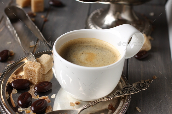Cup of espresso, sugar cubes and chocolate candy on rustic wooden background - Stock Photo - Images