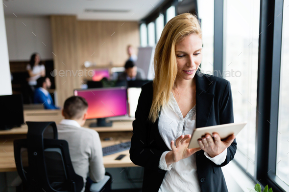 Portrait of successful businesswoman holding digital tablet - Stock Photo - Images
