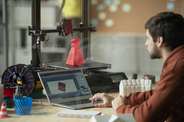 Young creative engineer or designer working over picture of new 3d model