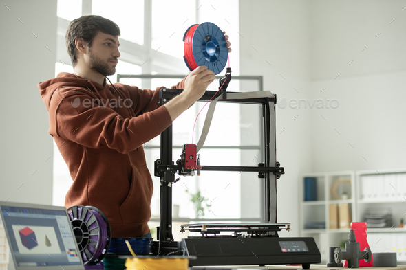 Young man putting new spool with red filament in 3d printer while going to print - Stock Photo - Images