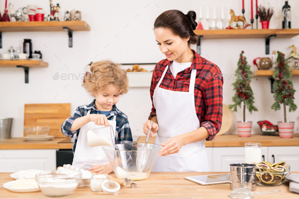 Little boy putting sugar into bowl with raw eggs while helping mother with dough - Stock Photo - Images