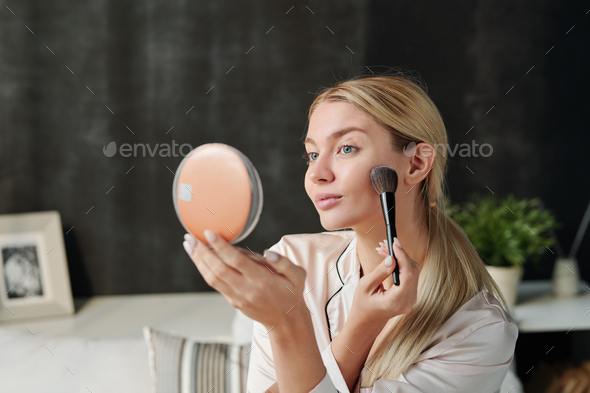 Pretty woman with brush applying powder on her face and looking in mirror - Stock Photo - Images