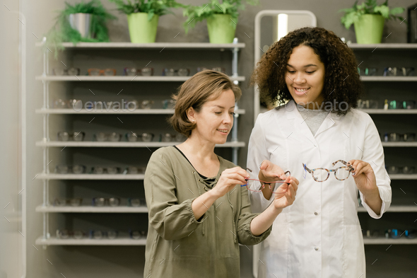 Young client of optics shop holding eyeglasses while listening to consultant - Stock Photo - Images