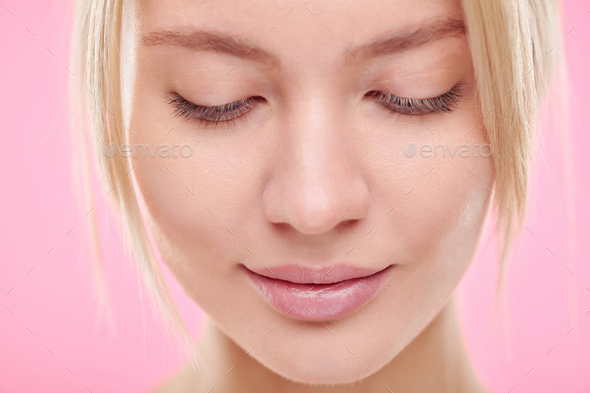 Face of young blond serene woman with natural makeup looking down - Stock Photo - Images