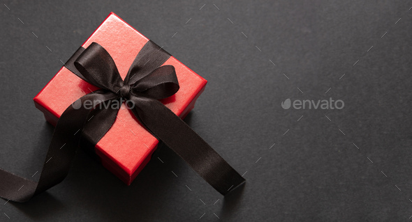 Gift box with black ribbon against black background, Black Friday concept. - Stock Photo - Images