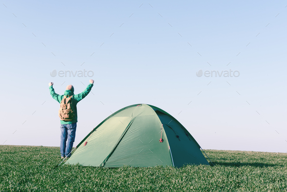 Tourist with hands up near his tent - Stock Photo - Images
