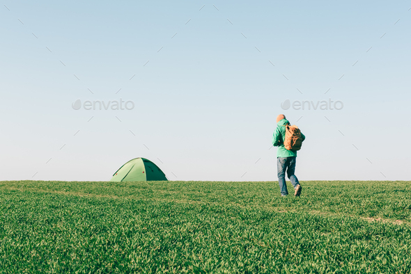 Tourist with backpack going to his tent - Stock Photo - Images