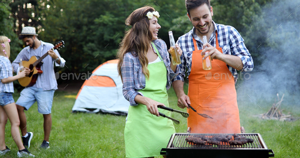 Friends spending time in nature and having barbecue - Stock Photo - Images