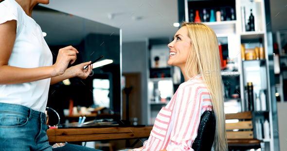 Makeup artist applying liquid tonal foundation on the face of the woman in make up room - Stock Photo - Images
