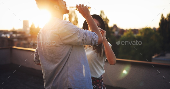 Young happy couple toasting with beer outdoors - Stock Photo - Images