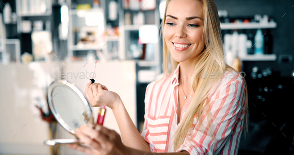 Young woman making make-up near mirror - Stock Photo - Images