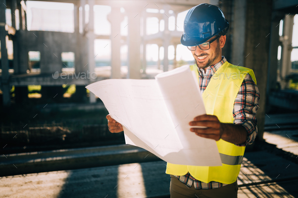 Portrait of male site contractor engineer with hard hat holding blue print paper - Stock Photo - Images