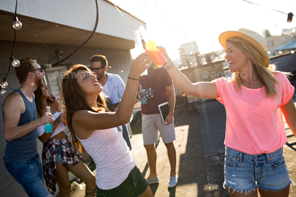 Young friends having fun at a rooftop party, playing the guitar, singing, dancing and drinking - Stock Photo - Images