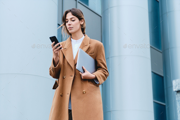Young confident casual businesswoman in coat with laptop using cellphone outdoor - Stock Photo - Images