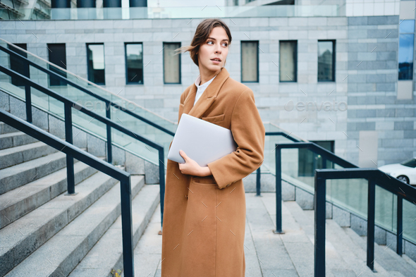 Young beautiful businesswoman in coat with laptop thoughtfully looking away outdoor - Stock Photo - Images