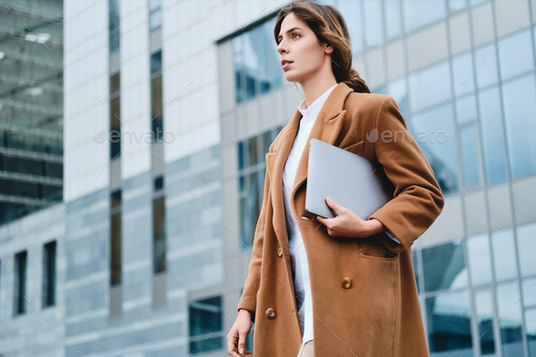Young serious businesswoman in coat with laptop thoughtfully walking through city street - Stock Photo - Images