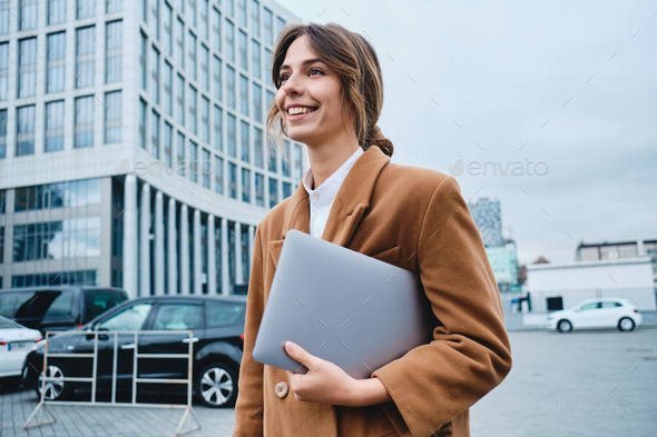 Young smiling lawyer in coat with laptop happily looking away walking through city street - Stock Photo - Images