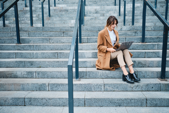 Young attractive businesswoman in coat confidently working on laptop on stairs outdoor - Stock Photo - Images