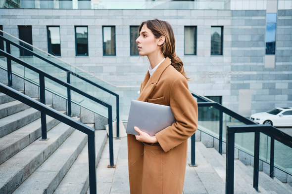 Side view of young gorgeous businesswoman in coat with laptop confidently looking aside outdoor - Stock Photo - Images