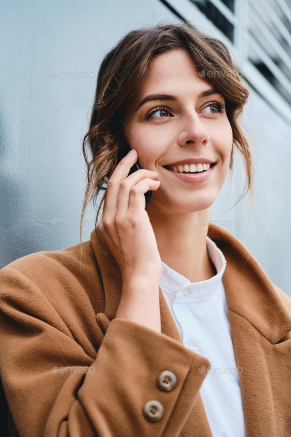 Young beautiful stylish businesswoman in coat happily looking away talking on cellphone outdoor - Stock Photo - Images