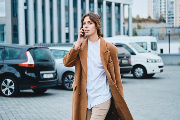 Young beautiful casual woman in coat with cellphone confidently walking through city street - Stock Photo - Images