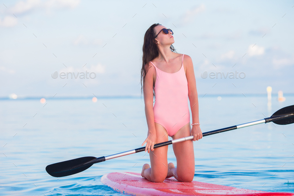 Beautiful young woman surfing on stand up paddle board at exotic vacation - Stock Photo - Images