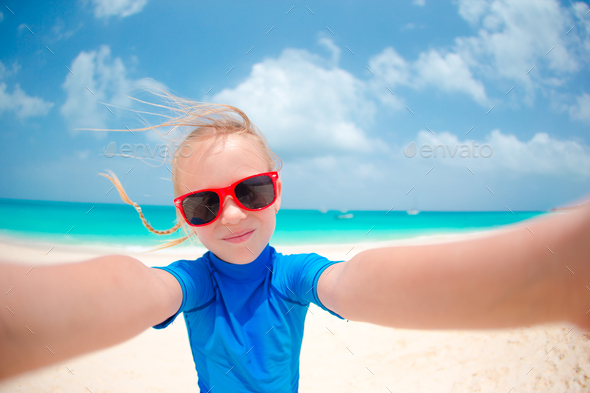 Adorable little girl making selfie at tropical white beach - Stock Photo - Images