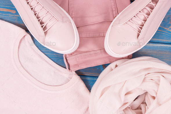 Womanly leather shoes, sweater, shawl and pants on old blue boards - Stock Photo - Images