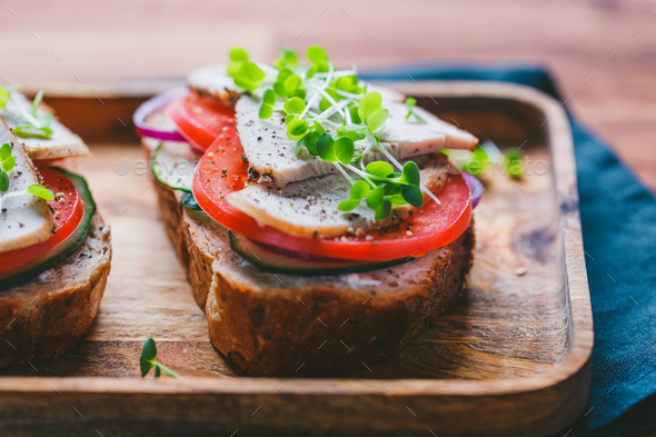 Sandwiches with turkey meat and fresh vegetables served with microgreens - Stock Photo - Images