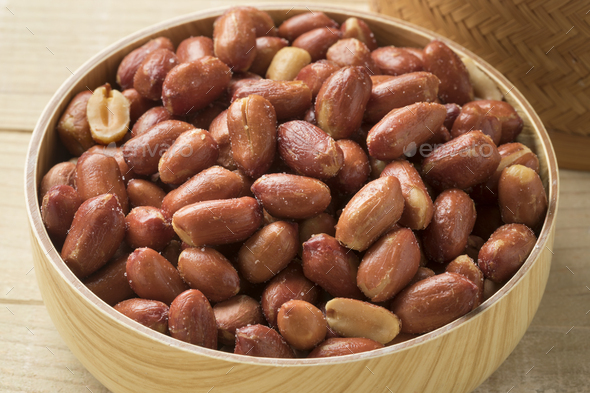 Wooden bowl with salted peanuts - Stock Photo - Images
