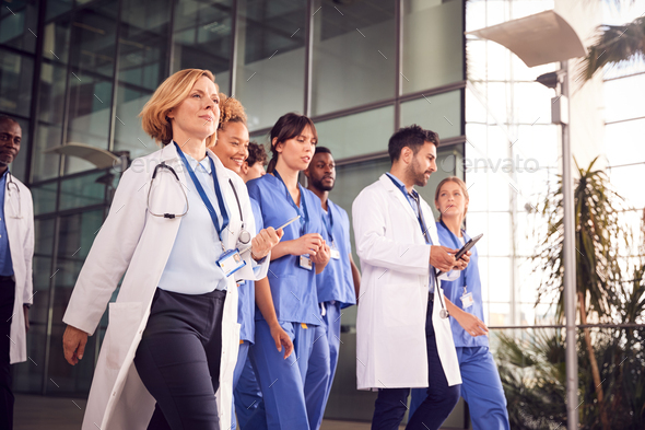 Medical Team Walking Through Lobby Of Modern Hospital Building - Stock Photo - Images